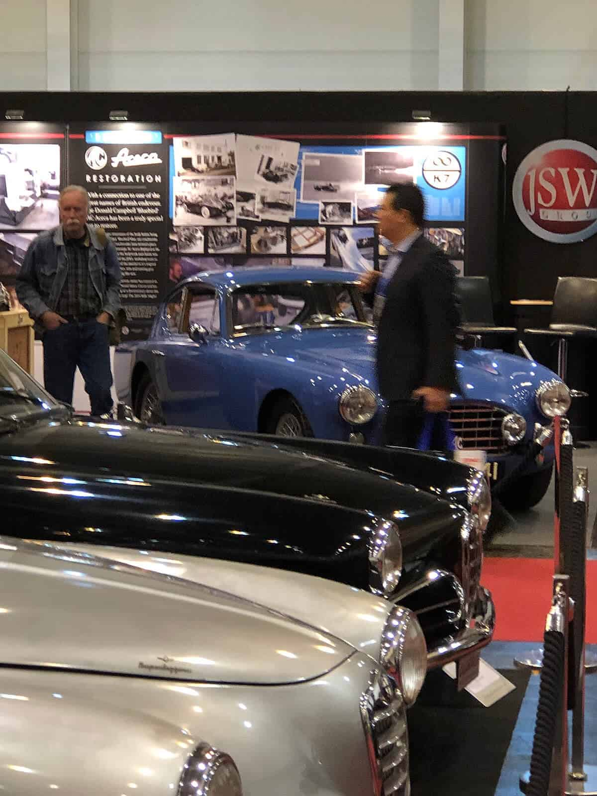 Front view AC Bluebird Aceca VPL441 on the JSW stand with a couple of Alfas in shot at 2019 Techno Classica Car Show in Essen
