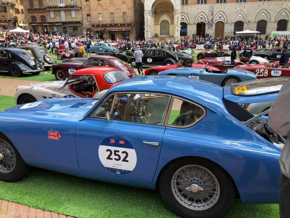 AC Bluebird surrounded by other fantastic cars in the Square in Siena on the 2019 Mille Miglia