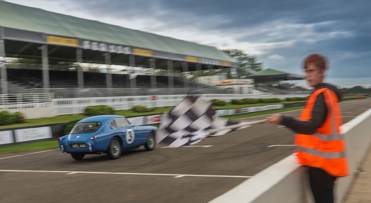 AC Bluebird crossing the finish line in first in class at Goodwood 2021 ACOC Club Sprint